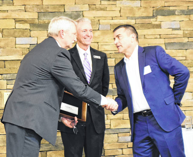 DJ Baird, 2018 Sidney-Shelby County Chamber of Commerce chair, congratulates incoming chair Phil Gilardi as Jeff Raible, chamber president and CEO, looks on.