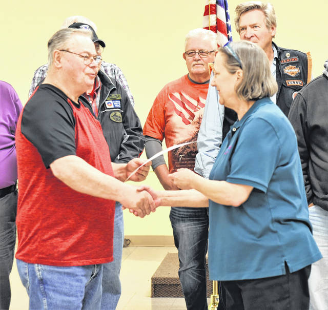 Donnie Campbell, left, of Anna, receives his certificate from Theresa Manteuffel for his service as a helicopter mechanic in Chu Lai, Vietnam, from 1968-1969 during a dinner Monday night which honored all Vietnam War veterans.