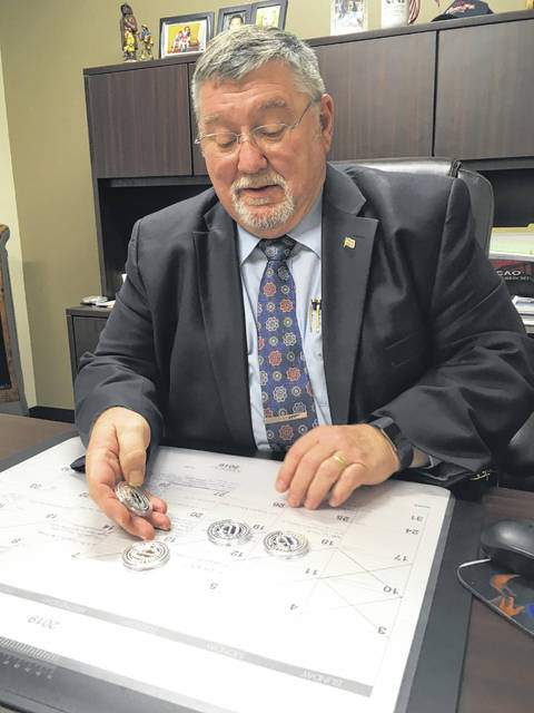 County Commissioner and Bicentennial Co-Chair Bob Guillozet examines the coins he recently picked up at Osborne Coinage in Cincinnati. A limited supply of the specially minted coins are available for sale at the offices of the Shelby County Commissioners during regular business hours.