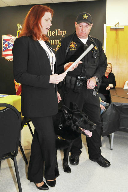 Shelby County Commissioner Julie Ehemann reads a proclamation for Colt during his retirement party.