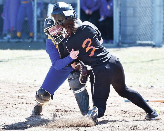 Minster's Emily Stubbs collides with Russia's Riley Hammonds at home plate after the ball got past Hammonds during a nonconference season opener on Saturday in Minster.