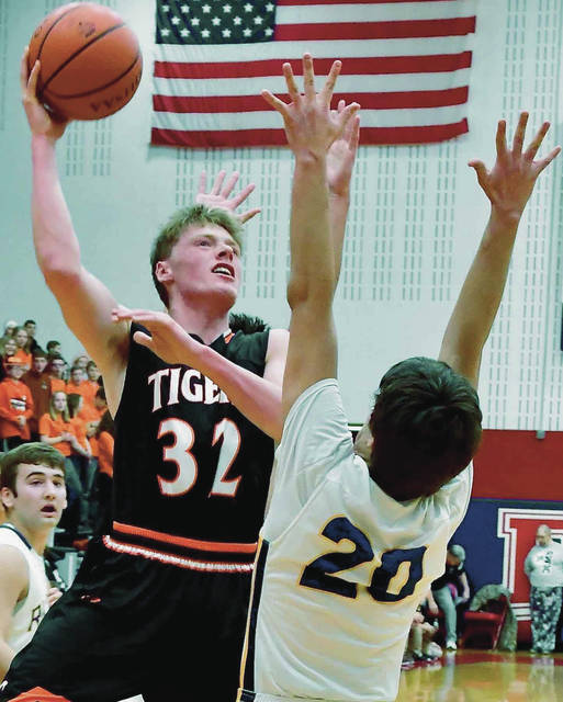 Jackson Center's Aidan Reichert shoots with pressure from Russia's Will Sherman during a Division IV sectional final on Saturday at Piqua's Garbry Gymnasium.