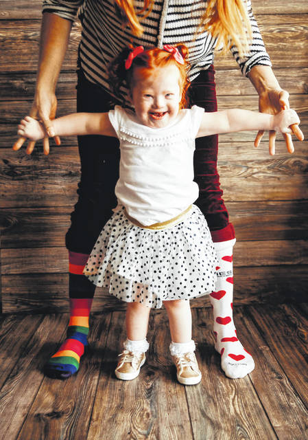 Gia Casiano, 2, of Sidney, enjoys celebrating World Down Syndrome Day with her mother, Julie, who wears mismatched socks for the occasion.