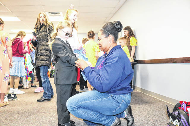 """Jenni Jeske, right, of St. Paris, fits Charli Curtner, 7, daughter of Cara and Dan McMann, of Sidney, and Ryan Curtner, of Sidney, in her costume as Delete, a character in """"Fairy Tale Misfits,"""" during a costume rehearsal in the County Extension Building in Sidney, Tuesday, March 12. The children's show will be presented by Sock and Buskin Players, March 16 and 17."""
