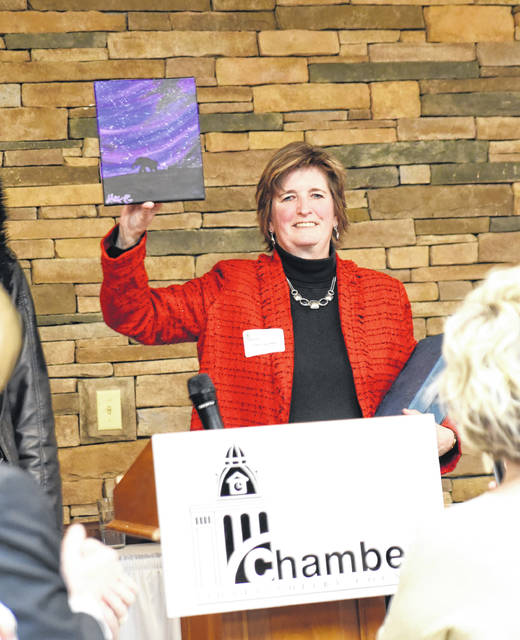 Cindy Helman holds up a painting her daughter, Alex, presented her Thursday night after Helman was named the Zenith Award recipient from the Sidney-Shelby County Chamber of Commerce.