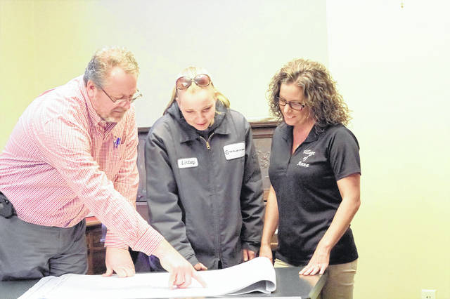 Anna Village Administrator Mike Homan, left, looks over plans with Public Works Superintendent Lindsey Alexander and Fiscal Officer Stacy Meyer in the Anna village offices, Monday, March 4. The plans outline a project due to begin this month that will extend water and sewer lines under the interstate to the east part of town.