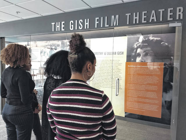 """Students attending the Black Issues Conference are shown standing outside the Gish Film Theater. They are reading the sign posted last week entitled """"Building a Just Learning Community,"""" which addressed the theater naming."""