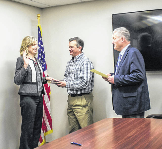 Shelby County Commissioner Tony Bornhorst administers the oath of office to Shelby County Auditor Amy Berning Monday morning. Holding the Bible during the ceremony is Berning's husband, Jeff. She was re-elected to office in November and her new term of office began Monday.