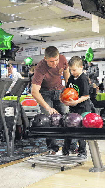 Big Brother Jaysen Rump, of Lewistown, teaches his Little Brother, Blake Fleming, son of Melisse Cassidy, how to bowl at Big Brothers Big Sisters of Shelby & Darke County's annual Bowl for Kids' Sake at Bel-Mar Lanes in Sidney, recently.