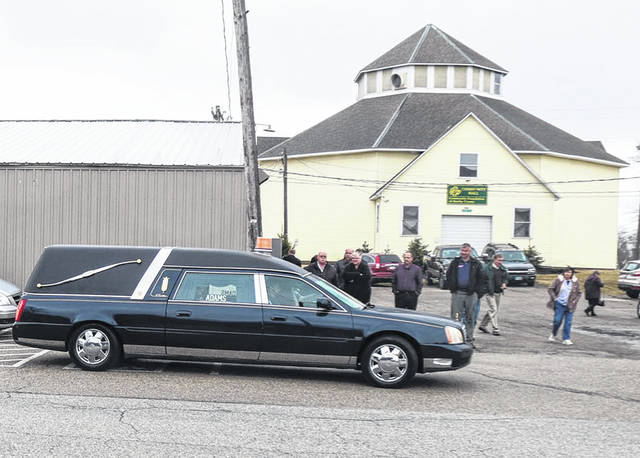 A hearse carrying the body of Shelby County Fair Secretary Jerry Schaffner begins a tour of the fairgrounds in Sidney, Friday, March 15, following Schaffner's funeral service as some of his many friends look on. His last ride around the facility he oversaw for 32 years preceded his burial in Shelby Memory Gardens in Hardin. Schaffner died March 11. Adams Funeral Home was in charge of arrangements.