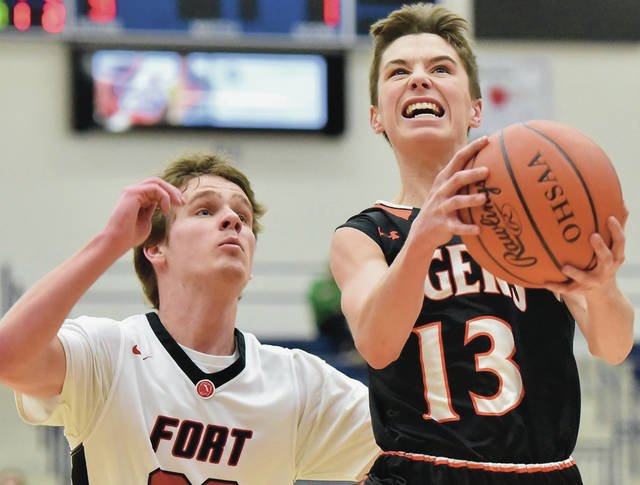 Jackson Center's Christopher Elchert shoots while defended by Fort Loramie's Eli Rosengarten during a Division IV regional semifinal on Tuesday at Kettering Fairmont's Trent Arena.