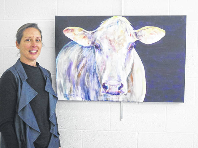 Lori Stallings, of Sidney, with one of her paintings featured in the Artist of the Month exhibit at the Amos Memorial Public Library in Sidney.