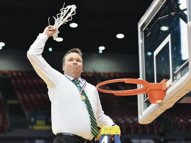 Anna coach Nate Barhorst waves the game net after Anna defeated Clark Montessori 68-59 in a Division III district final on Sunday at UD Arena. It's the first district title for Anna during Barhorst's eight-year tenure.