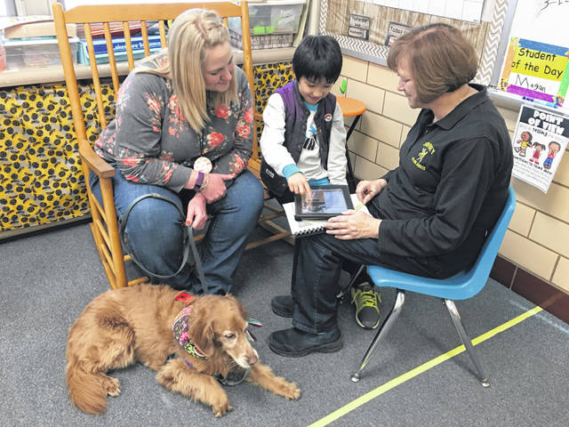 ELL teacher Amy Stratton, far right, works with student Yota Saruyama as he interviews his teacher Amy McGill, left, who is pictured with her dog, Emma.