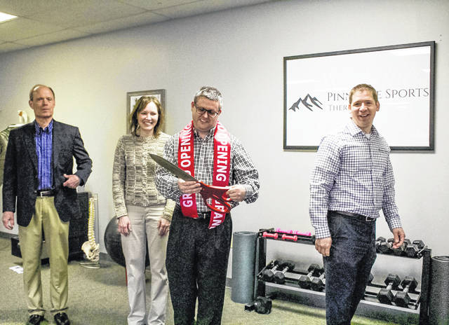 Fort Loramie Mayor Randy Ahlers, left, Lois Spitzer, of Versailles, second from left, and Nate Barhorst, right, president of the Fort Loramie Chamber of Commerce, celebrate with Jim Spitzer, center, following a ribbon-cutting ceremony that opened the Spitzers' physical therapy clinic, Pinnacle Sports Therapy, in Fort Loramie, March 5.