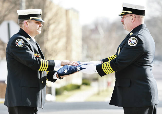 City of Sidney Deputy Fire Chief Cameron Haller, left, accepts a U.S. flag from Sidney Fire Chief Brad Jones during a flag ceremony for Haller who has retired from the Sidney Fire Department. The ceremony was at Sidney Fire Station 1, Friday, March 1.