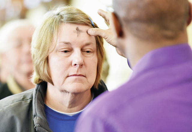 Deb DeLoye, left, has a cross of ash drawn on her forehead by Dimitri Williams, both of Sidney, during an Ash Wednesday service at Holy Angels Church Wednesday, March 6. The ash cross symbolizes that people were made by God from dust and will return to dust. Ash Wednesday marks the beginning of Lent a time of abstinence and fasting.