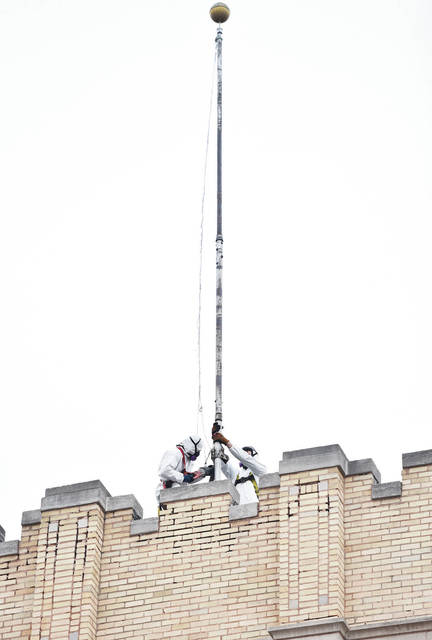 Men in full body suits and wearing air filtering masks work on the flag pole on top of the Ohio Building recently. The long unused building is getting a new roof. Bricks have been falling off the Ohio Building onto the sidewalk, requiring the city to block off sidewalk from pedestrians.