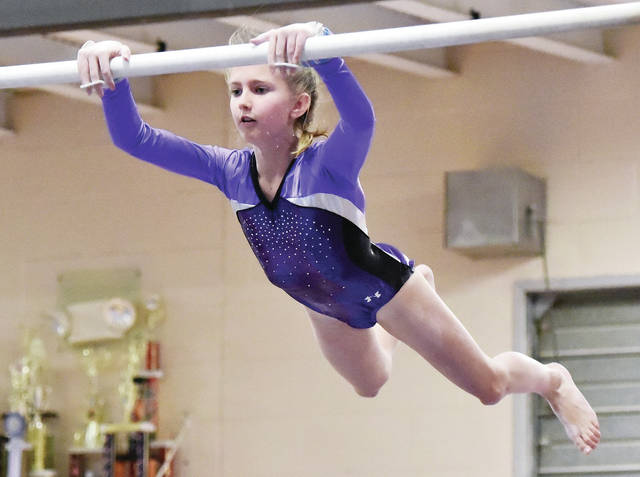 Janelle Siegel, 10, of Fort Loramie, daughter of Mike and Janet Siegel, performs on the uneven bars for judges during the SW Ohio & Indiana Gymnastics Championships at the Sidney Shelby County YMCA Saturday, March 16. The competition had a circus theme.