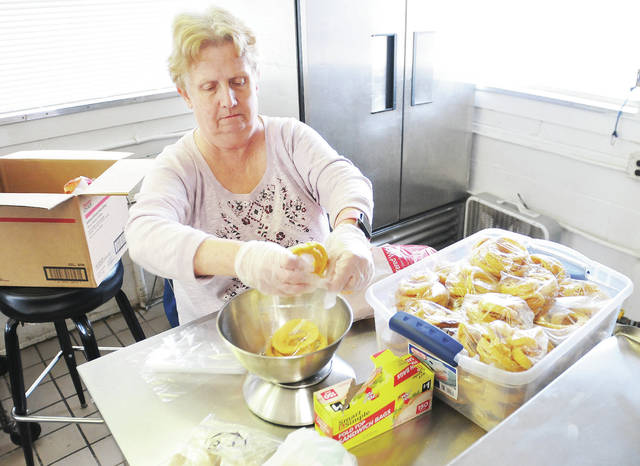 Susan Poore, of Sidney, packs onion rings into individual baggies, Wednesday, March 20, at the BK Rootbeer Drive-In, in preparation for the drive-in's season opening, Thursday, March 21. The B & K Rootbeer Drive-In is open 11 a.m. to 8 p.m. Monday through Saturday and noon to 7 p.m. Sunday.