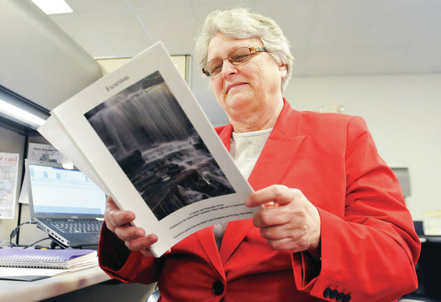 "Betty Paulus, of Russia, looks through a copy of ""Excursions,"" an Edison State Community College publication that includes one of her essays, in the Sidney Daily News advertising office, Thursday, March 21."