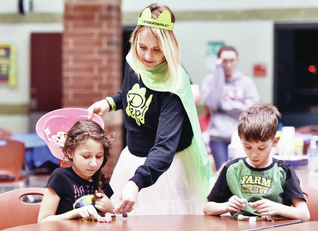 SCARF PEP! Leader Chastity Crowder, center, of Lockington, hands out suckers to Chasmine Shawler, left, 8, of Sidney, daughter of Jasmine Shawler and David Livermore, and Jordan Wade, 8, of Houston, son of Samantha Griffin and Brandon Griffin and Jordy Wade. The kids were supposed to give away three of the suckers and tell the people they gave them to what they had learned from Crowder about how to take care of a pet.