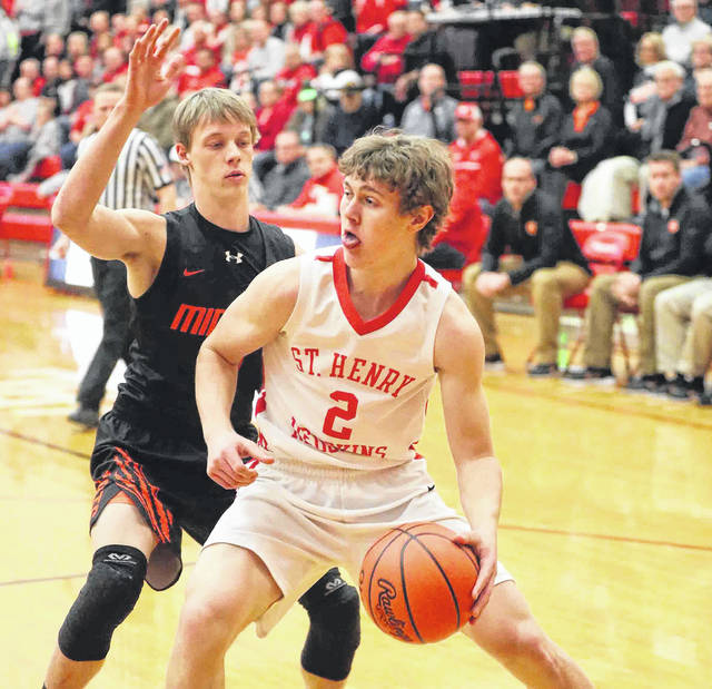 Minster's Noah Enneking guards St. Henry's Jay Knapke during a Division IV district semifinal on Tuesday at Wapakoneta.
