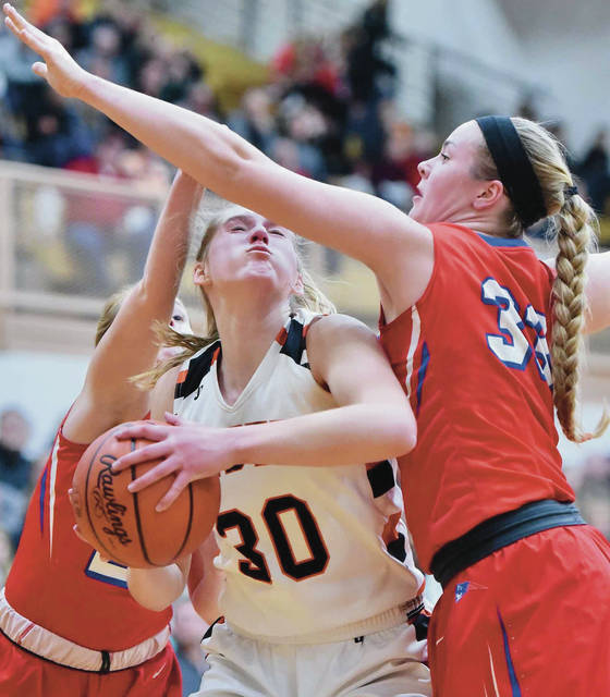 Minster's Courtney Prenger looks to shoot while covered by Tri-Village's Maddie Downing during a Division IV regional semifinal on Thursday at Vandalia-Butler's Student Activities Center.