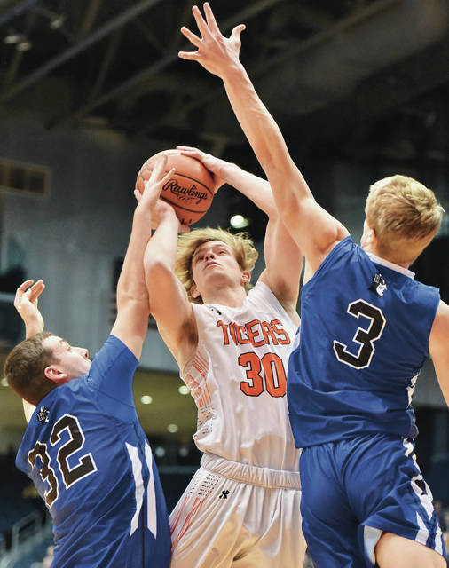 Versailles' Evan Hiestand shoots with pressure from Cincinnati Reading's Nash Morgan and Gabe Van Skaik during a Division III district final on Sunday at UD Arena. Hiestand scored 12 points and had eight rebounds.
