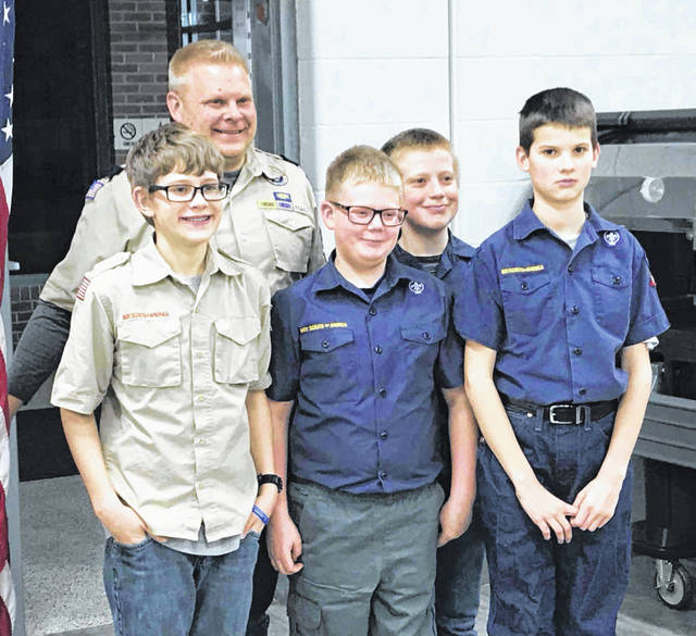 "Cubmaster Kevin Meyer, back, poses with Cub Scouts, from left to right, Eli Huwer, Carter Korte, Ben Meyer and Henry Hanson after awarding the Scouts their ""Arrow of Light"" awards during the Minster Cub Scout Pack 44 meeting on Monday, March 11, at the high school cafeteria. The four Weblos II Cub Scouts participated in a ""Crossing Over"" ceremony as they completed their Cub Scout program. The ""Arrow of Light"" award, which is the highest award they can earn, can be displayed on their Boy Scout uniform when they join."