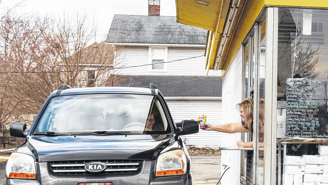 Karen Jenkins, in car, gets a slushy from Deb Motsinger at Chilly Jilly's in Sidney. The popular treat spot opened for the season March 16.