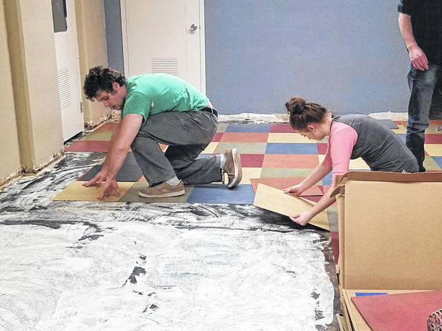 Chuck Adkins, left, and Hannah Haeberlin, both of Sidney, seniors at Christian Academy Schools, lay tile in the Church at Affton during a mission trip to St. Louis, recently.
