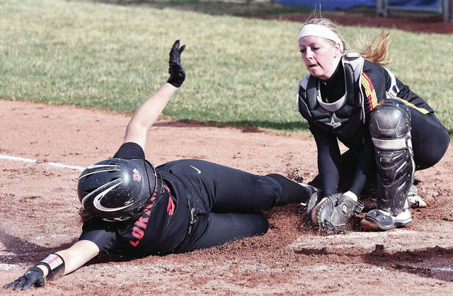 Fort Loramie's Aleah Frilling slides safely into home as New Bremen's Marissa Topp tries to tag her during a nonconference game on Friday in Fort Loramie.