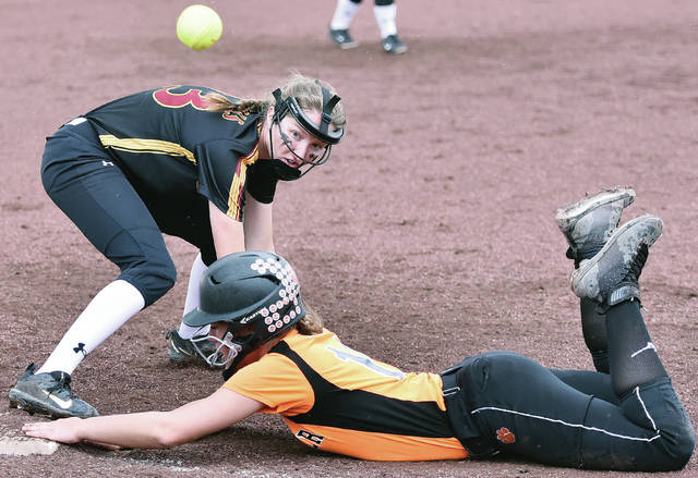 New Bremen's Kira Bertke watches a throw go by as Minster's Taylor Homan dives back to third base during a Midwest Athletic Conference game on Thursday in New Bremen.