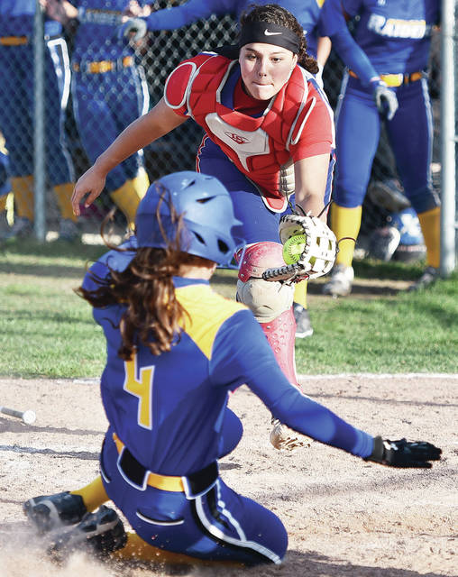 Riverside sophomore catcher Jalynn Stanley looks to make a tag as Russia's Ava Daniel slides into home plate in the seventh inning of a nonconference game on Tuesday in Russia. Daniel was ruled safe on the play, but Stanley made a force out at home soon after to end the inning and give the Pirates a chance to rally.