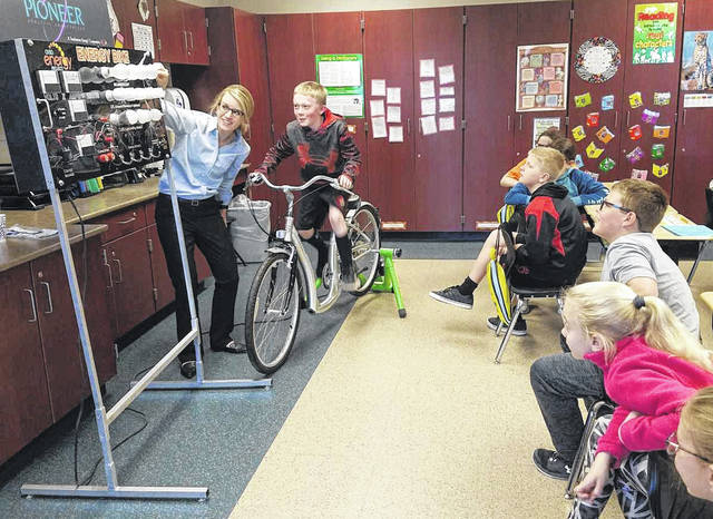 """Jodi Boerger from Pioneer Electric facilitates as fourth-grader Jackson Frilling tests out the """"Energy Bike."""" Jackson is the son of Adam and Jessica Frilling, of Fort Loramie."""