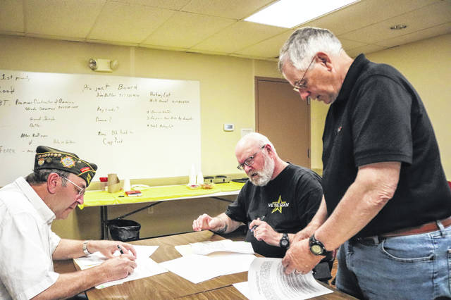 Mike Bennett, part of the committee helping to form the Sidney Veterans Association, hands paperwork to VFW Commander Dennis Thatcher, left and American Legion Commander Jim Moorman to sign completing the merger of the two veterans organizations.
