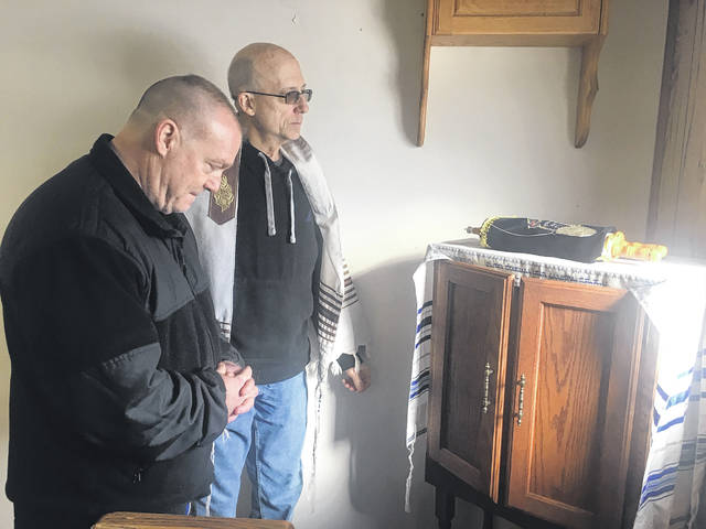 Bruce Campbell and Jim Richardson pray over the Torah scrolls housed at 417 Linden Ave. The scrolls were later walked to 121 W. Poplar St. to allow it to be set as the new home for their studies.