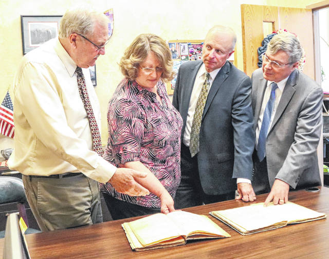 Sheriff John Lenhart, Clerk of Courts Michele K. Mumford, Prosecutor Timothy S. Sell and and Common Pleas Judge James F. Stevenson inspect Shelby County's first minutes book and appearance docket on Monday afternoon in the Shelby County Courthouse.