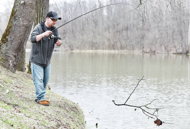 Dustin Miller, of Sidney, hauls in a branch from Tawawa Lake on Friday, April 5. The branch contained a bobber ensnared in it from an unlucky fisherman. Miller was fishing for large mouth bass. The only thing he had caught when the photograph was taken was the branch.