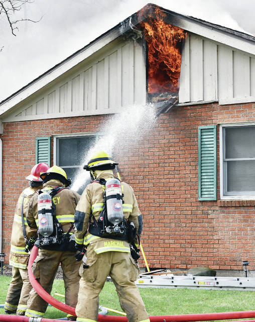 Sidney firefighters battle a fully involved house fire at 2021 Old English Court on Wednesday, April 10. The Sidney Police Department reported that Sidney Police rescued a man and two dogs from the house at 11:33 a.m..