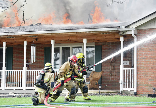 Sidney firefighters battle a fully involved house fire at 2021 Old English Court on Wednesday, April 10. The Sidney Police Department reported a man and two dogs were rescued from the house. The fire started at about 11:30 a.m. Lockington and Anna fire departments also responded.
