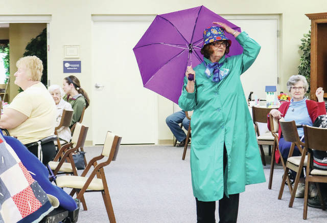 Pam Gilbert, of Sidney, a volunteer who participates in Ohio Living - Dorothy Love's line dancing, models a rain coat at Ohio Living Dorothy Love's Spring Tea Tuesday, April 9. All clothing modeled came from the Twice Around Shop at Ohio Living - Dorothy Love.