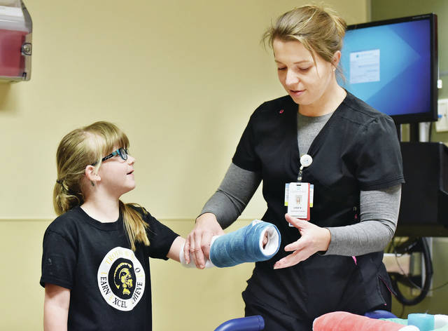"Zoey Wehrman, left, 6, of Botkins, daughter of Robyn and Jared Wehrman, has a cast put on her arm by emergency room registered nurse Lisa Vondrell, of St. Marys, during a ""Make Believe Hospital"" at Joint Township District Memorial Hospital on Thursday, April 11. Students from around the area took part in the learning experience to alleviate common childhood fears and misconceptions about hospitals. Students rotated through stations that taught kids about different aspects of a hospital."