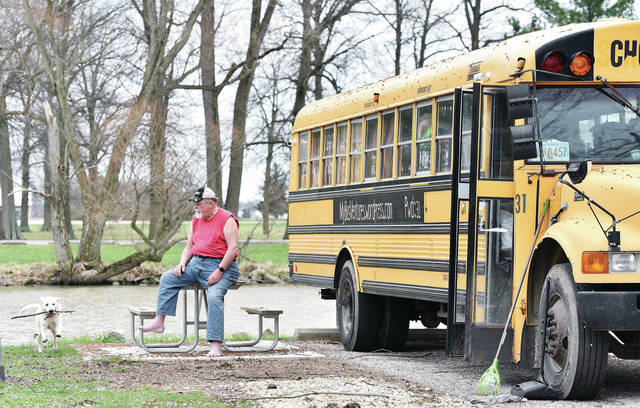 Alan E. Elsass, waits for his dog Precious Babe to return a stick while camping at the Lake Loramie State Park campground Friday, April 12. Elsass sold his house in Decatur, Ill., and bought a school bus Feb. 4, 2016. On March 6, 2016, Elsass got into his school bus and started traveling across the U.S.A.. Elsass has now been to 49 states (Hawaii being too expensive) in his bus along with his service dog Babe. Elsass grew up in Waynesfield, Ohio. Elsass has a blog of his travels at mybusventures.wordpress.com. The password is 31. Elsass plans on leaving the campground on Sunday, April 14.