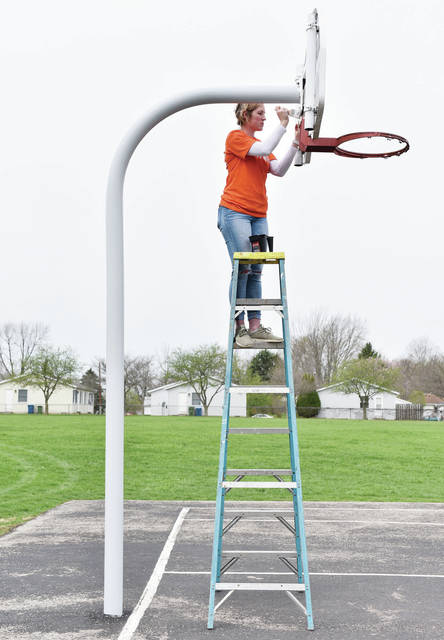 Wilma Valentine Center employee Hannah Starkey, of Sidney, paints a basketball hoop.
