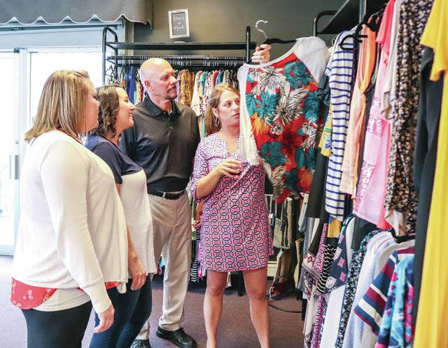 Jessica Hammaker, left to right, and Ashley Himes, both of Sidney watch as Sidney Flower Shop owners Mike and Betsy Martin show them clothing that's being sold in the flower shop during a Business After Hours event recently.