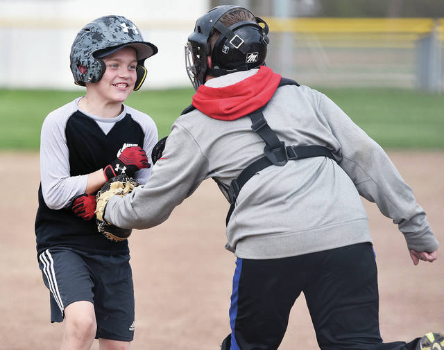 Dalton Davis, left, 11, son of Bridget and Dallas Davis, gets tagged out by Bryce Allen, 13, son of Jeremy Allen, all of Sidney, at home plate during a baseball practice at Custenborder Field, Wednesday, April 17.