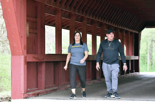 Christy Devore, left, of Jackson Center, and Chad Dailing, of Piqua, go through the Ross Bridge while on a longer walk through Tawawa Park on Wednesday, April 24. The covered bridge was constructed in 1971.