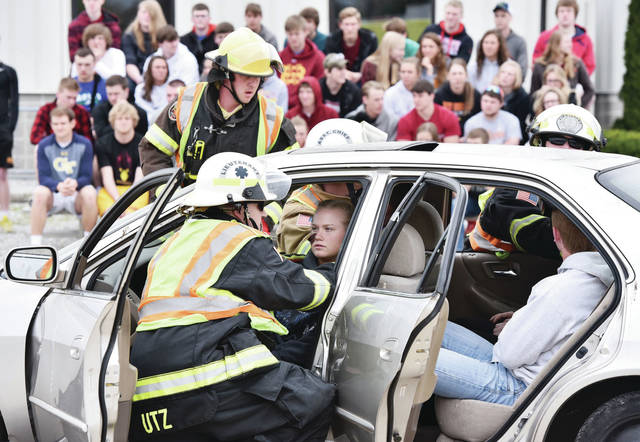Sarah Parker, 17, of New Bremen, daughter of Robert and Michelle Parker, sits in the front drivers seat of a car while taking part in a mock crash exercise. The mock crash was held behind New Bremen High School Wednesday, April 24 to show New Bremen students the potential consequences of impaired driving.